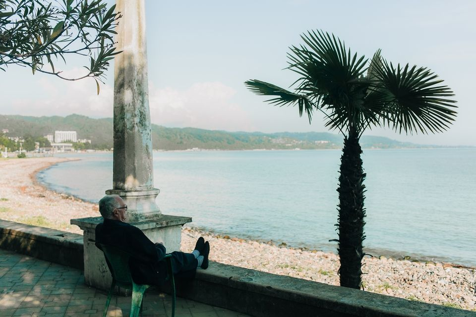 man sitting in a chair with his feet up overlooking the beach and ocean.