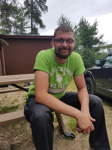 Me sitting on a bench with a cottage in the background.