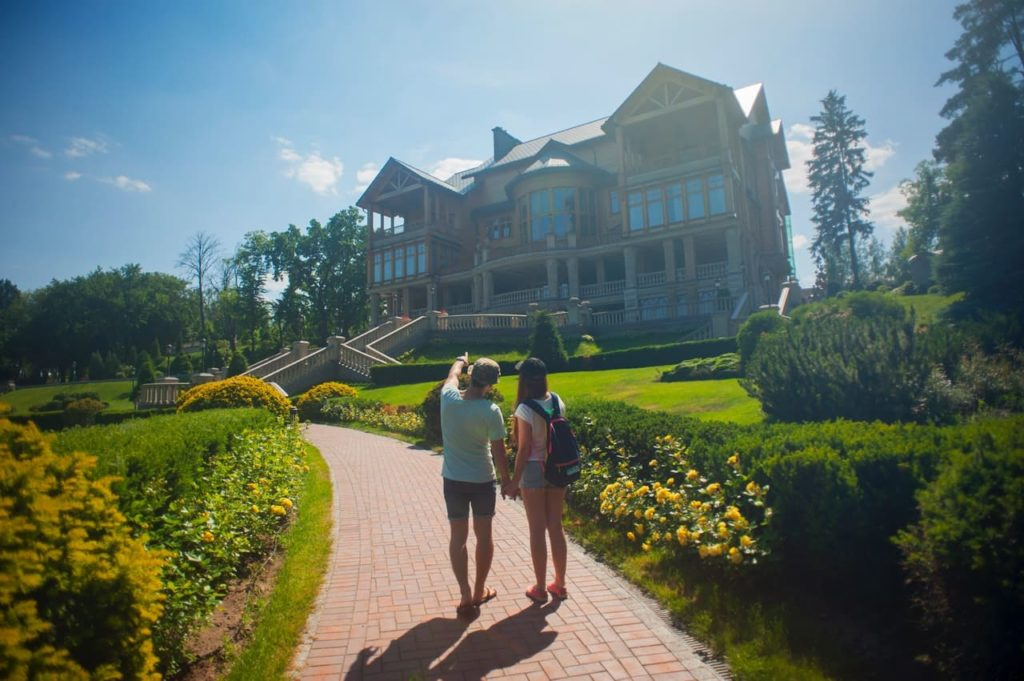 couple standing in front of a large house