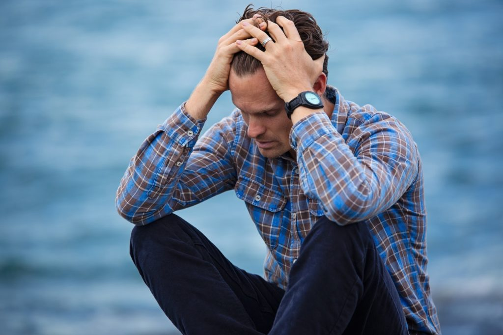 man in blue shirt sitting with his hands on his head worried.