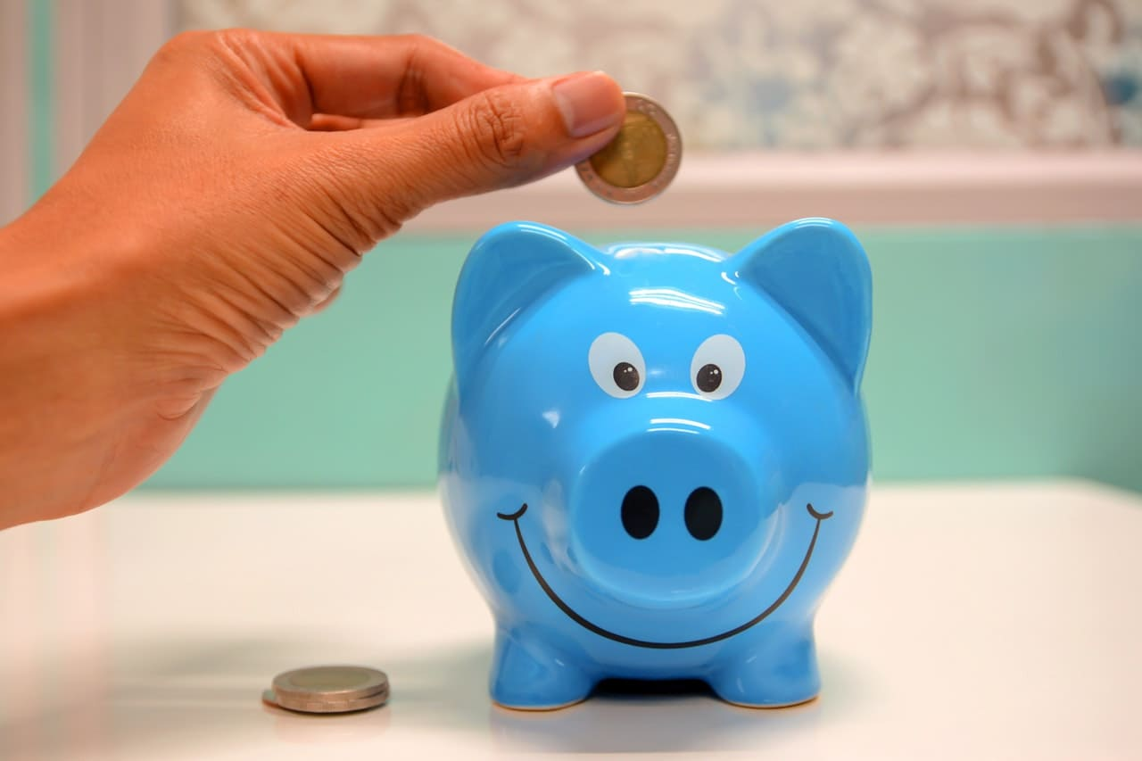 person putting coins into a blue piggy bank
