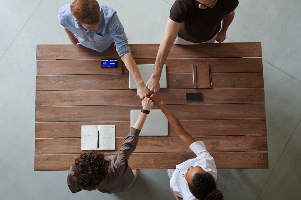 four people at a table doing a fist bump above their work.