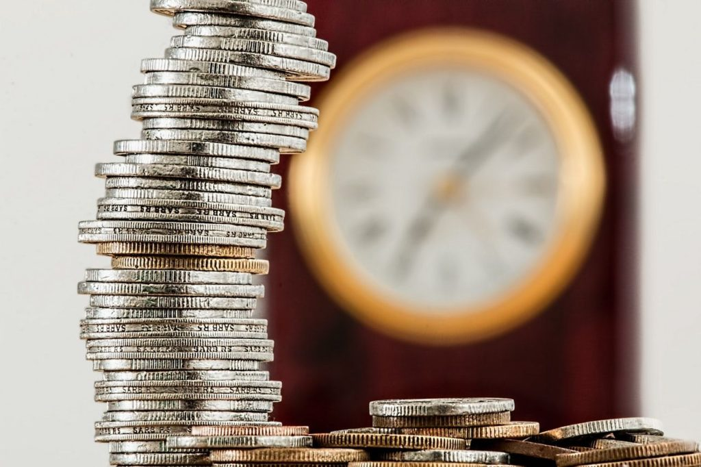 A stack of gold and silver coins with a clock in the background.
