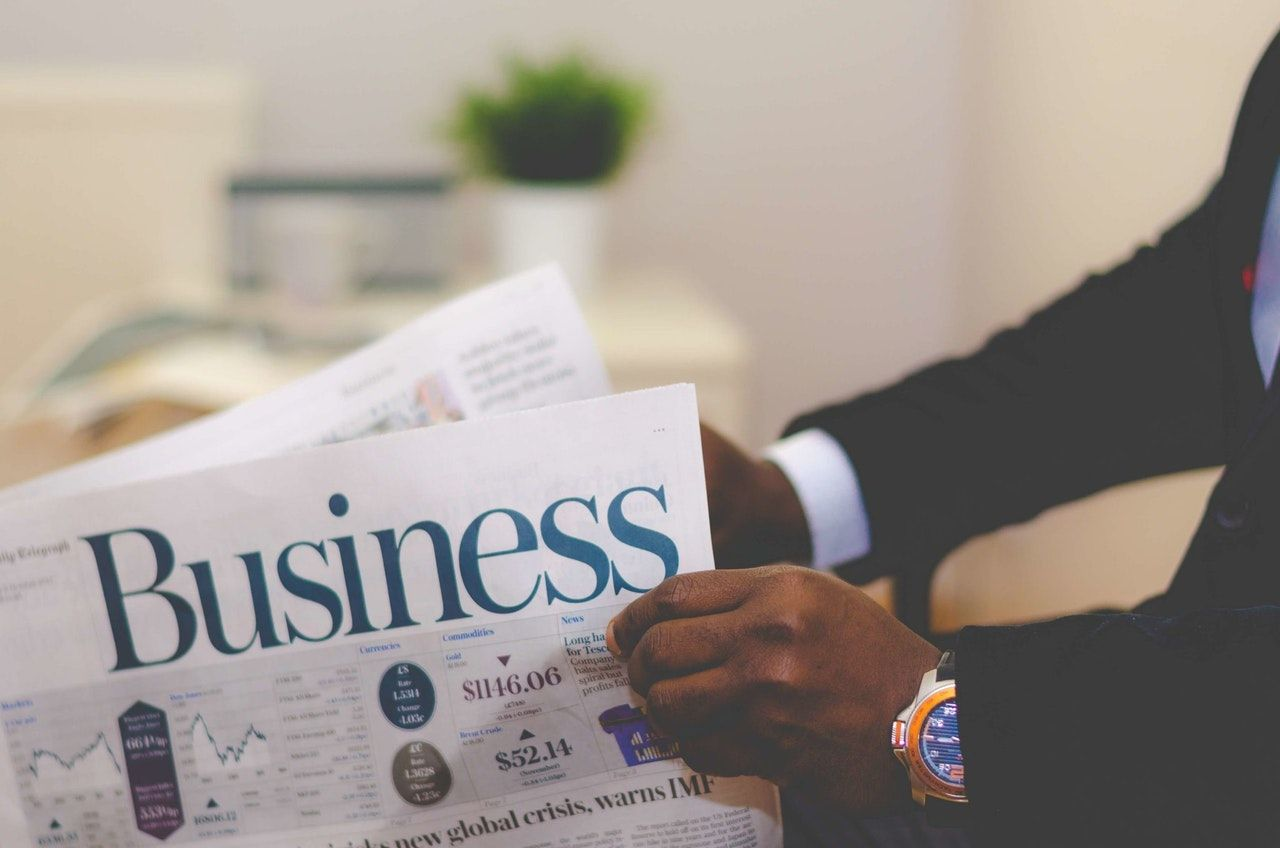 person holding the Business section of a newspaper