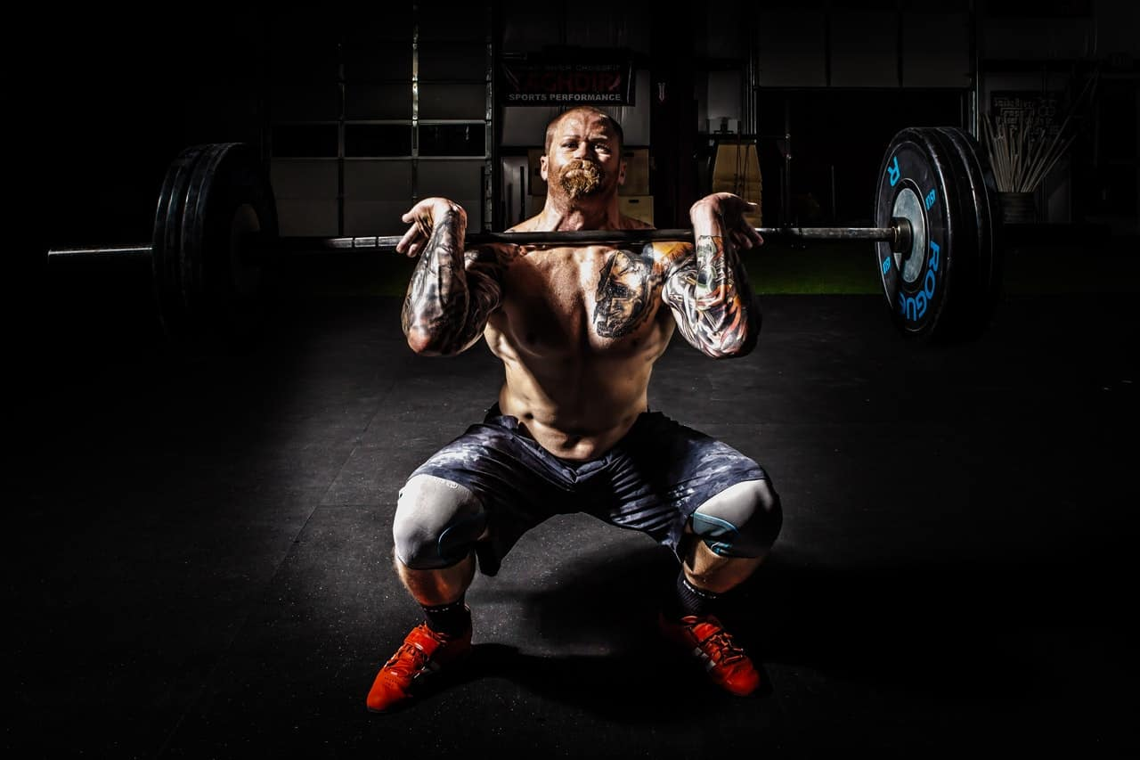 man front deadlifting a barbell