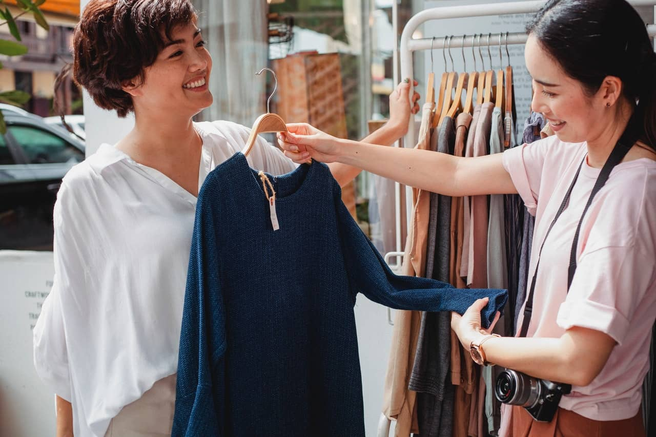 two girls shopping together to buy clothes
